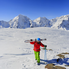 Freeride - Man with skis climbs to the top