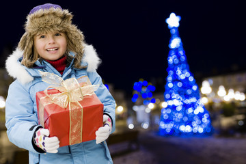 Christmas night, lovely girl with Christmas gift