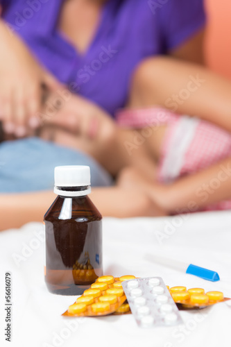 Pills and thermometer with a sick girl in the background
