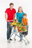 Family shopping. Cheerful family standing near shopping cart