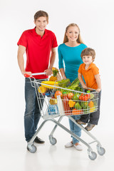 Family shopping. Cheerful family standing near shopping cart