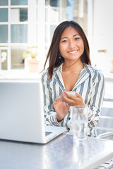 Cheerful asian businesswoman texting