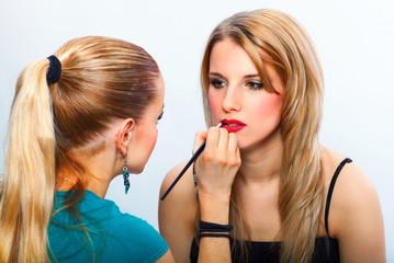 Make-up artist applying lipstick on model's lips