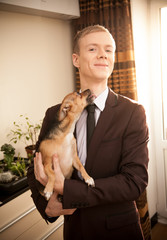 Small dog licking man in dark suit