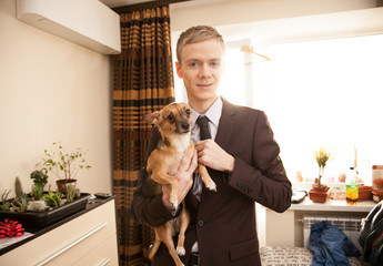 Handsome man holding small dog on hands