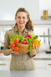 Happy young housewife holding plate full of vegetables
