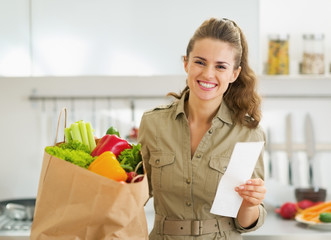 Smiling housewife with check and shopping bag full of vegetables