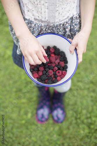Girl With Bowl Of Fresh Wild Blackberries And Raspberries