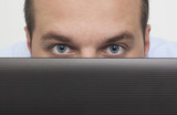 man peeking over laptop