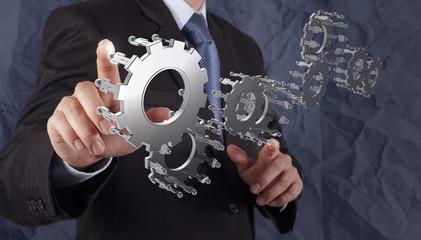 businessman hand shows gear to success concept