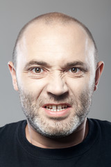 portrait of angry man isolated on gray background
