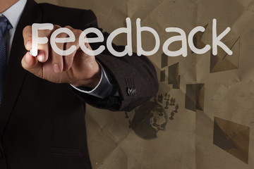 businessman hand writing Feedback with recycle paper background