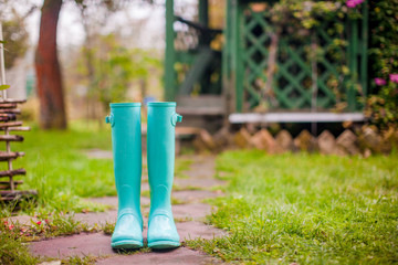 Bright mint rubber boots in the garden summer house background