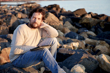 Smiling man with tablet on beach with rocks