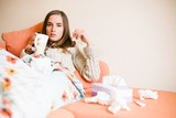 Young woman with cold / flu lying on couch and drinking tea