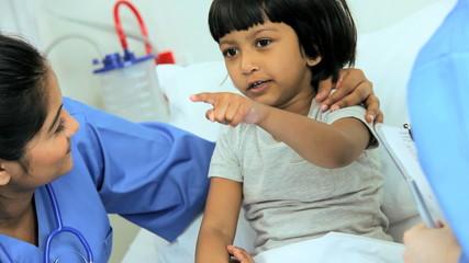 Multi Ethnic Nursing Staff Recording Child Patient Treatment