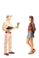 Full length portrait of a delivery boy holding a bunch of flower