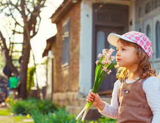Adorable girl smelling flowers in a rustic garden