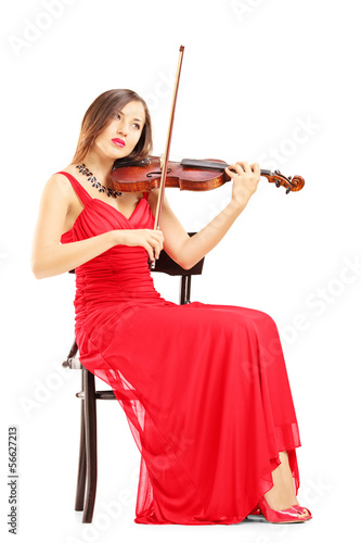 Full length of a woman in red dress playing the violin