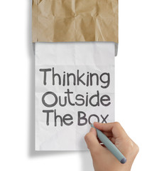 hand draws thinking outside te box on crumpled paper