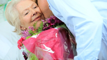 Son Visiting Elderly Mom Hospital Bringing Flowers