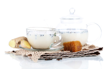 Teapot and cup of tea with milk and spices