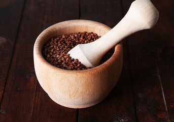 Buckwheat groats in bowl on wooden background