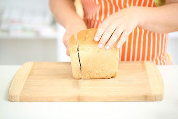 Woman slicing bread on chopping board, close up