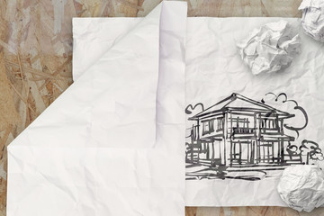drawing house on wrinkled paper as concept