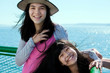 Two happy girls smiling on ferry deck with ocean in background