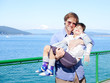 Father holding disabled son in arms on deck of ferry boat.