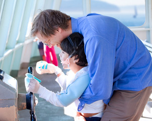 Father helping disabled son play with the ferry's steering wheel