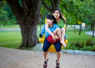 Big sister holding disabled brother on special needs swing at pl