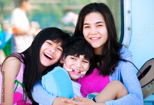 Two sisters taking care of disabled little brother