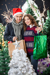 Couple With Shopping Bags Standing At Christmas Store