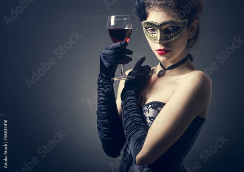 young woman in carnival mask and a glass of red wine.