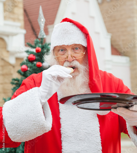 Santa Claus Eating Cookie Against House