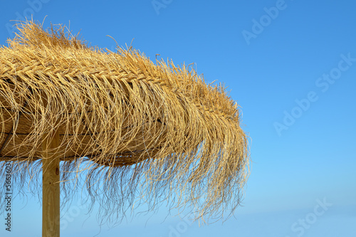 Natural beach umbrella on blue sky - 56636031