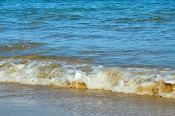 Sea waves crashing on sundy beach