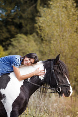attractive brunette female rider embracing her horse