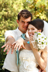 beautiful young bride and groom show their wedding rings