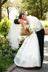 beautiful young bride and groom hug in love summer park outdoor