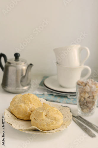 Breakfast with eclair on light background