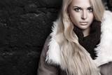 Beautiful blond woman in fur near bricks wall. winter fashion
