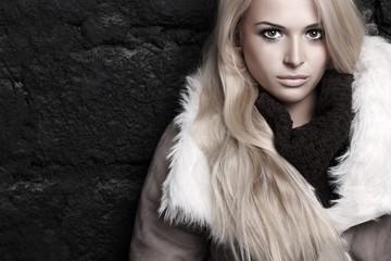 Beautiful blond woman in fur near bricks wall. winter fashion