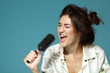 Cheerful attractive teen girl sing song holding comb like a micr