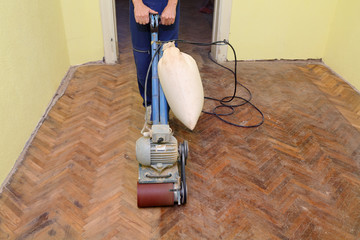 Worker polishing parquet floor with grinding machine
