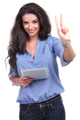 casual woman with tablet shows victory