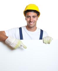 Lachender Bauarbeiter mit Werbetafel