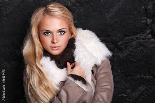 Beautiful blond woman in a fur near bricks wall.winter style